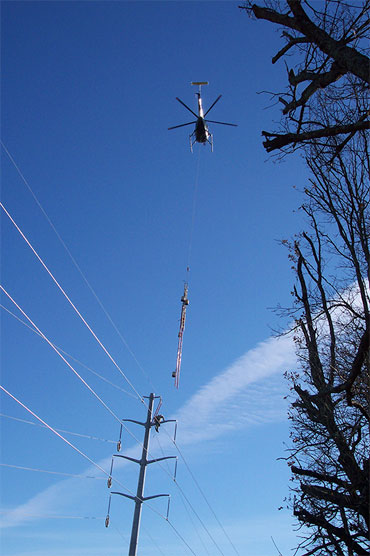 Photo of helicopter hovering over power lines